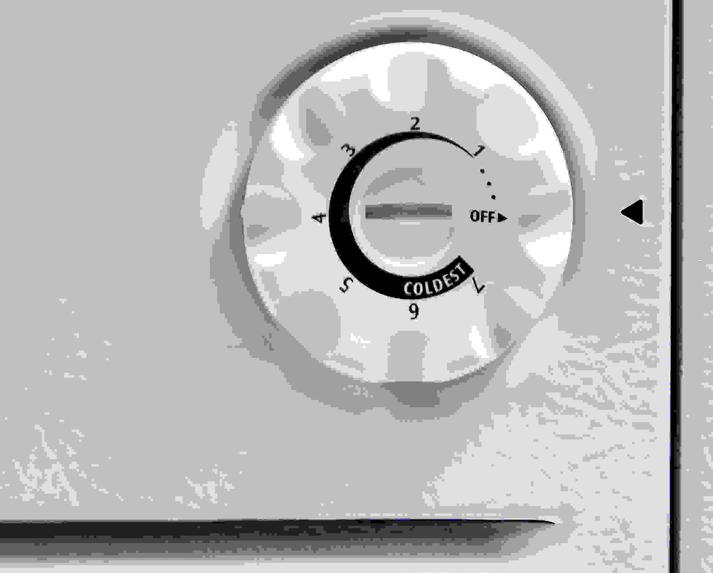 A standard dial thermostat is found near the bottom of the Kenmore 16542 on its left side.