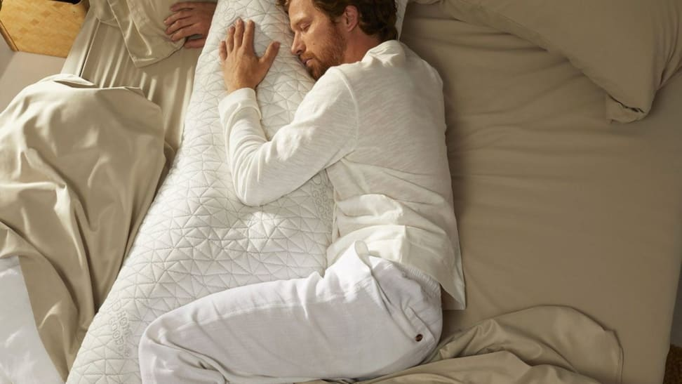 A man curls up with a Coop Home Goods body pillow