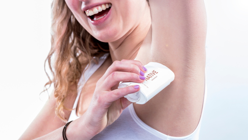 A woman applying deodorant to her armpit