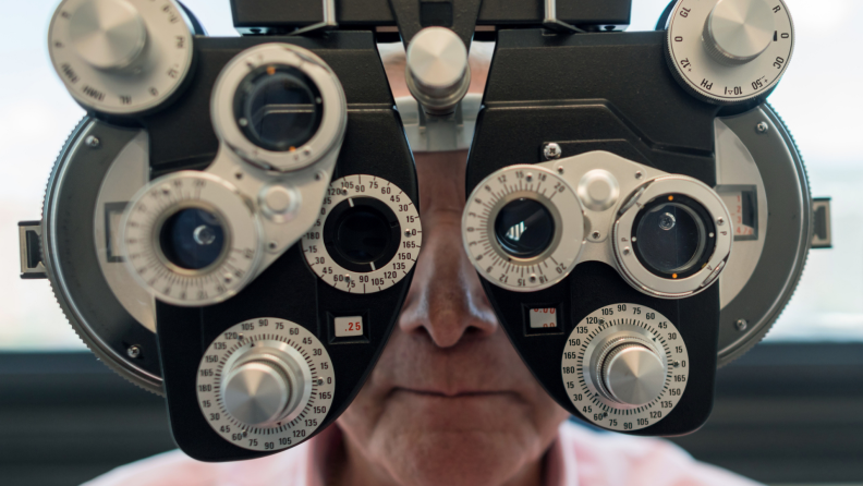 A senior patient looks through a device at an optometrist.