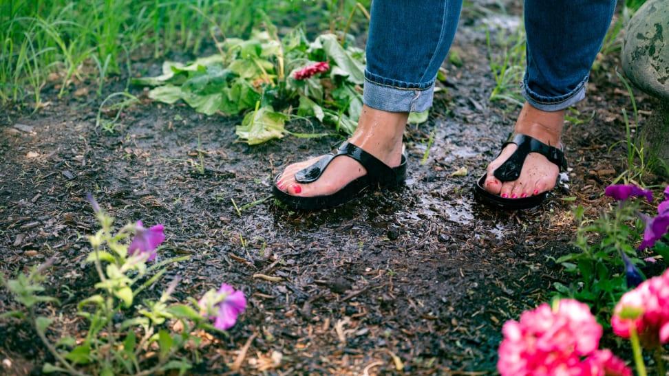 Girl wearing waterproof Birkenstock sandals stands in a garden.