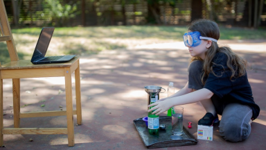 Girl doing science experiment outside
