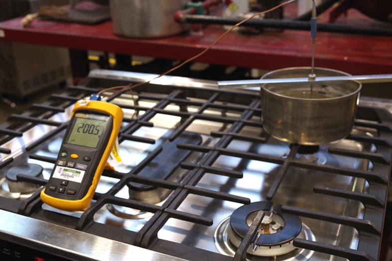 A temperature gauge rests in boiling water.