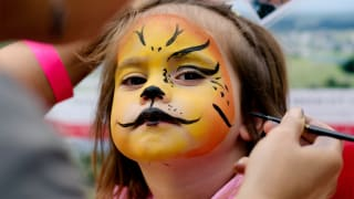 A child getting her face painted to look like a lion for Halloween.