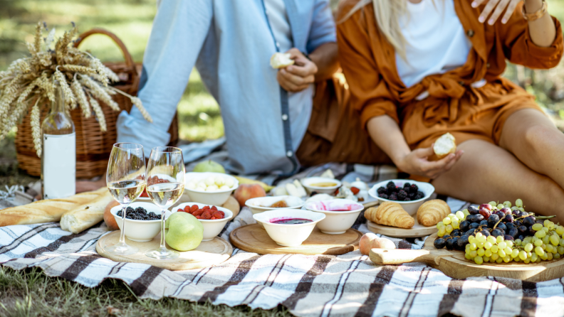 A couple enjoys an idyllic outdoor picnic, complete with grapes, bread, fresh fruit, and a bottle of wine.