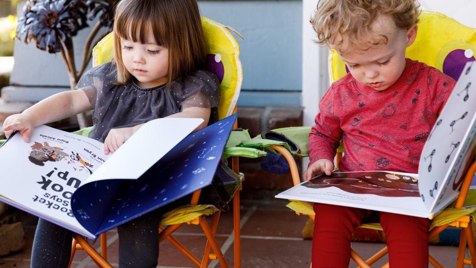 Two children read picture books outside.