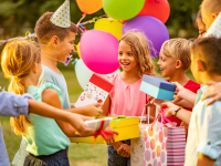 A group of children at a birthday party giving the birthday girl gifts
