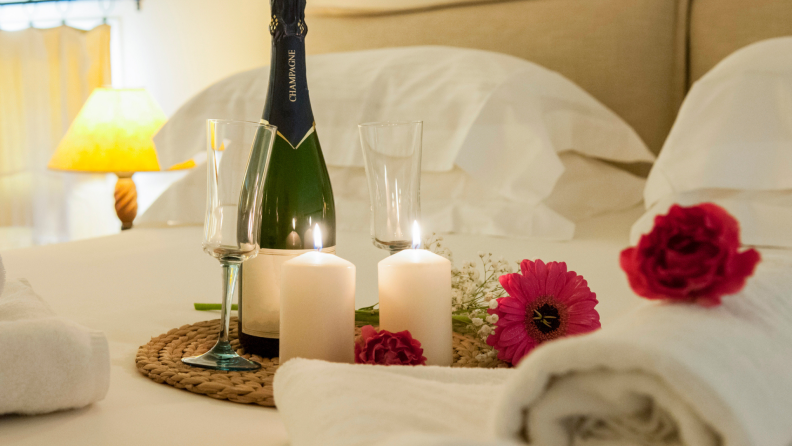 A Valentine's Day arrangement on a bed: towels, flowers, two lit candles, a pair of glasses, and a bottle of Champagne.