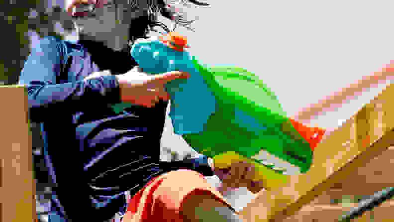 A boy uses the Nerf Dino-Soak Super Soaker