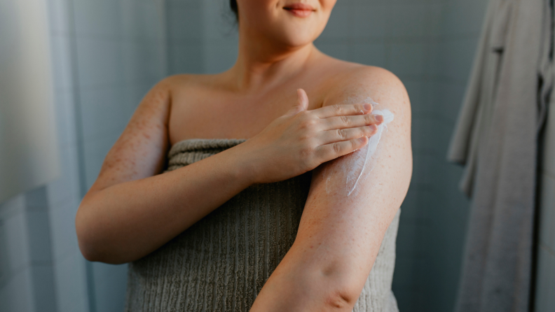 Person rubbing moisturizer on arm after showering.