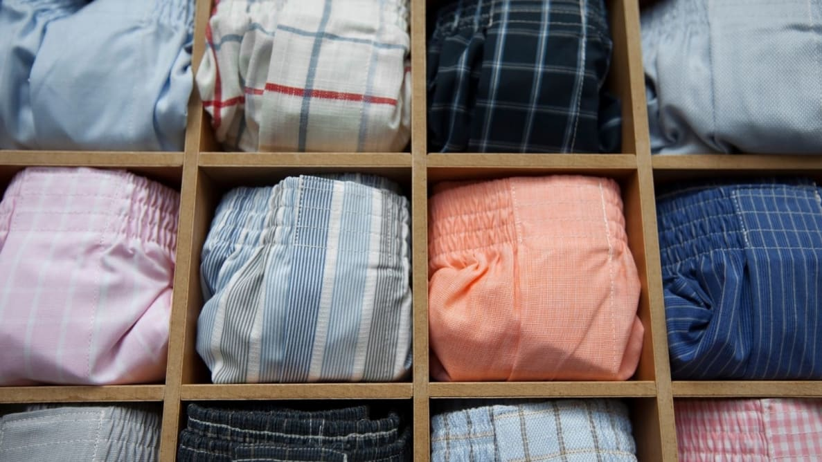 Rows of colorful folded boxer briefs inside of wooden storage.