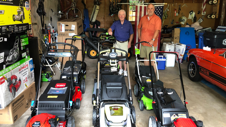 Two testers stand with eight lawn mowers in a garage.