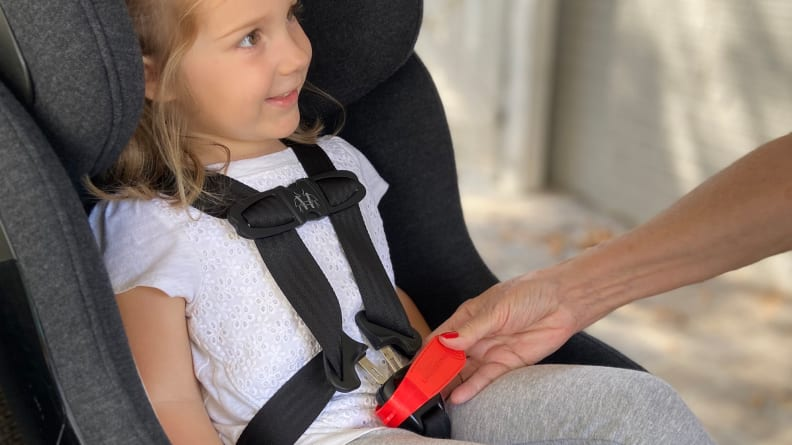child in carseat that is being buckled in