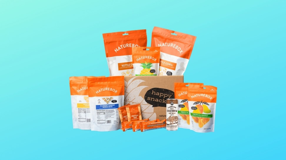 An assortment of NatureBox snacks are clustered together in front of a blue gradient background. The snacks are packaged in white bags with text on the front and a thick orange band at the top. Snacks include blueberry almond quinoa bites, dried mango, kettle corn, and more.