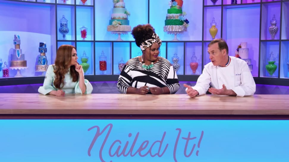 A still from the series Nailed It! featuring host Nicole Byer and Jacques Torres at the judge's table.