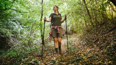 Girl hiking in the woods with walking sticks.