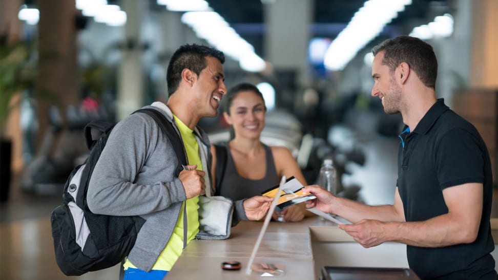 A man and a woman talking to a gym employee at the front desk.