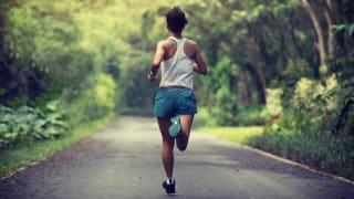 back of woman running in park wearing blue shorts and white tank top.