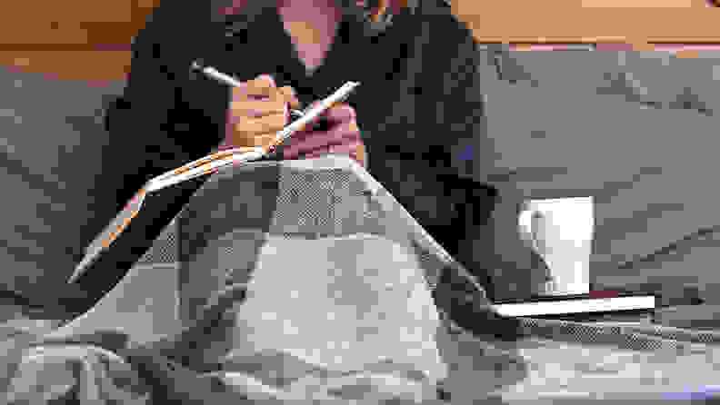 A photo of a woman writing in a journal.