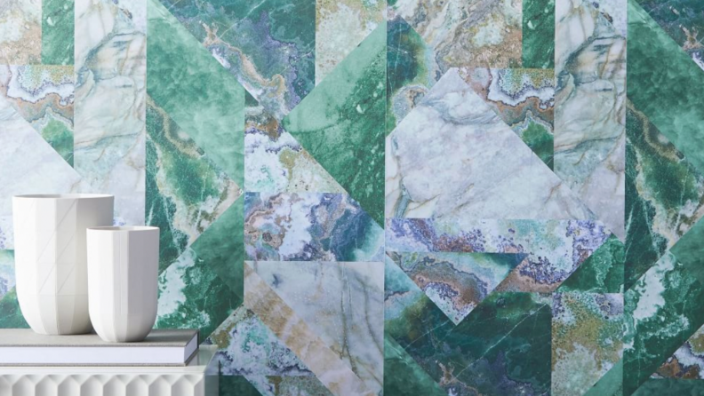 Green, blue and gray faux marble wallpaper with white vases on the bottom left corner of the frame.