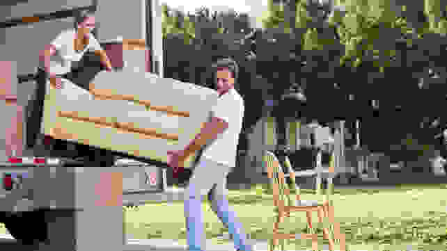 Man and woman loading couch into a truck
