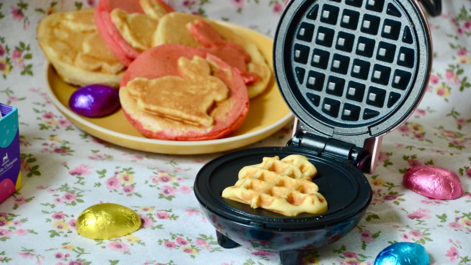 A bunny-shaped waffle is in the Dash Bunny mini waffle maker. Some cooked waffles are in the floral background, as are the Easter egg chocolate.
