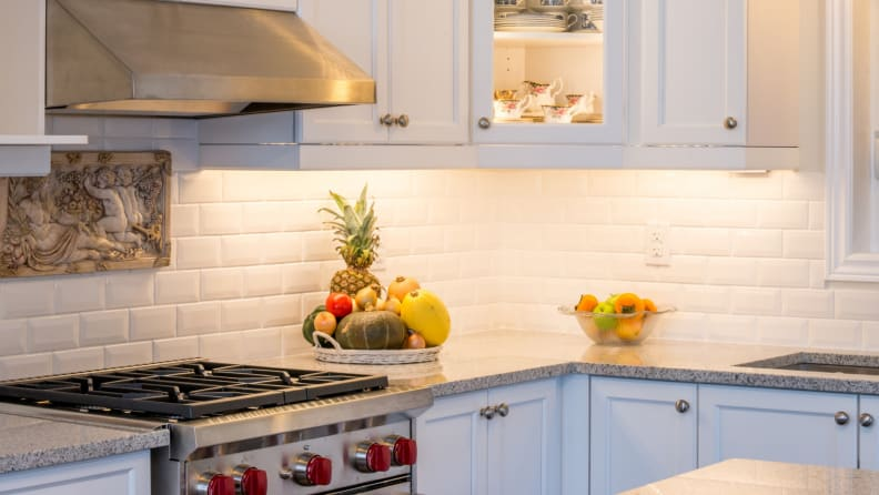 A kitchen is lit by cabinet lighting.