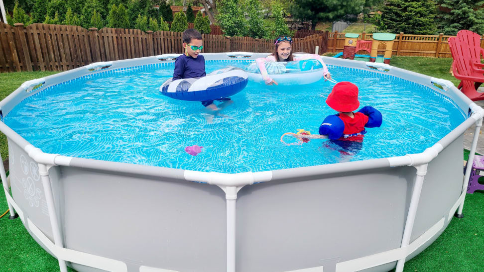 Three children swim and play in an above-ground Intex pool.