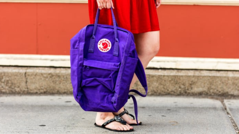 Person carrying a purple backpack down the sidewalk.
