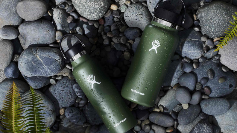 Two green Hydro Flask water bottles laying on a stone path.