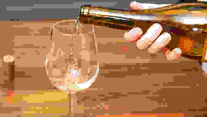 Pouring a glass of white wine into a white wine glass