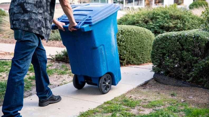 A person takes out the recycle bin to the curb.