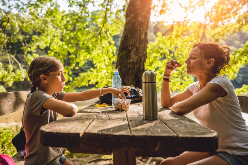 Woman and kid sit at table and share snacks