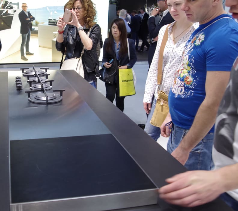 Crowd at Design Week Looks at Stainless Cooktop