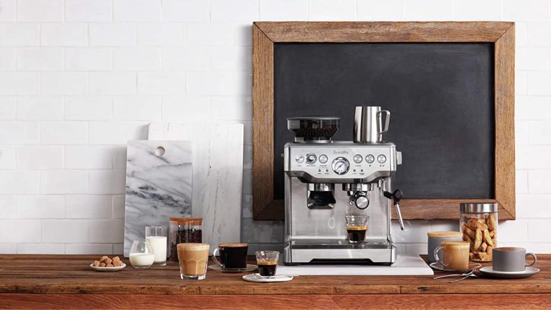 A Breville espresso machine sits on a counter.