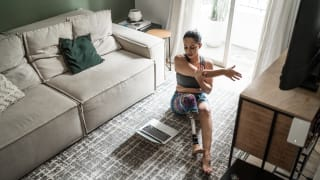 Person with prosthetic leg stretching on living room floor in front of laptop screen.