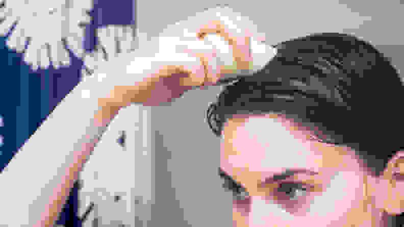 A person holding a HiBar shampoo bar to their brown hair in the shower.
