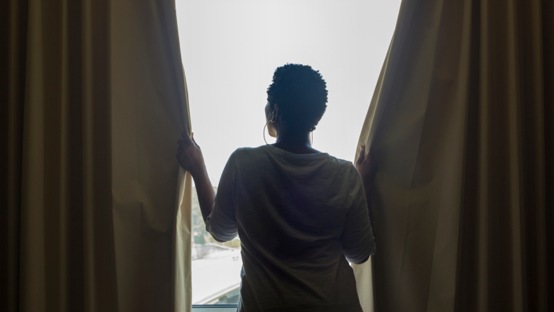 Person's silhouette opening or closing long curtains in front of a window