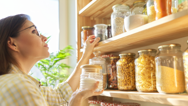 A woman holds a jar of sugar inside her organized pantry full of canned items.