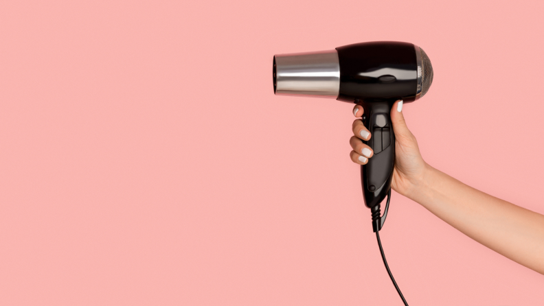 A hang holding a black blow dryer against a pink background
