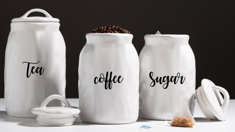Three ceramic canisters that store tea, coffee, and sugar.