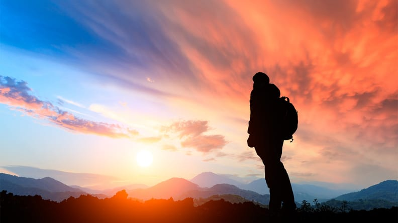 An image of a person staring at a sunset while hiking.