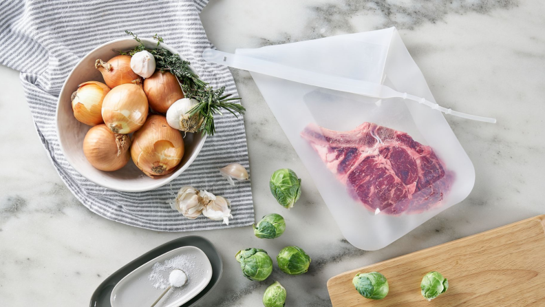 A piece of steak is inside a Stasher silicone bag surrounded by a bowl of onions, garlic, herbs, Brussels sprouts.