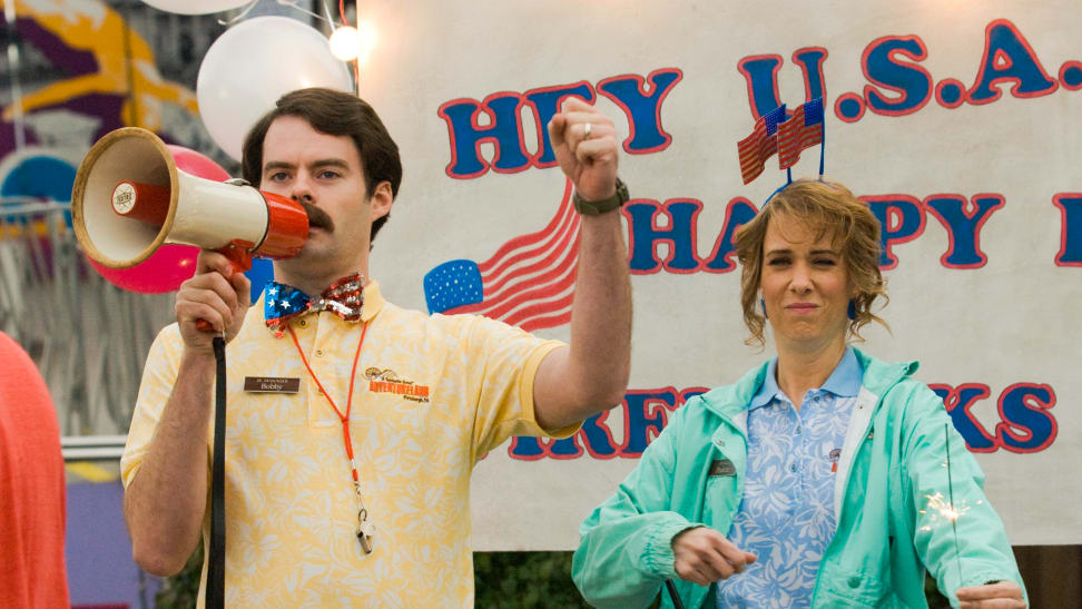 Bill Hader shouts into a megaphone in the 2009 comedy Adventureland. Standing next to him is fellow SNL alum Kristen Wiig.