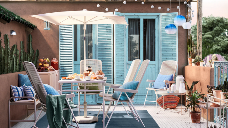 A vintage-inspired set of patio furniture sits on a balcony.