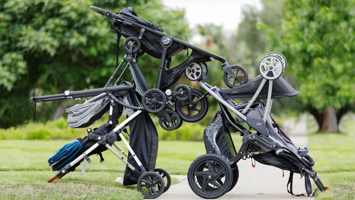 Photo of several strollers arranged on a park sidewalk.