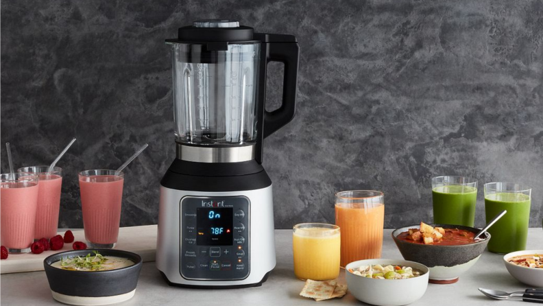 An image of an Instant blender seated on a countertop surrounded by smoothies in glass cups and fruit.