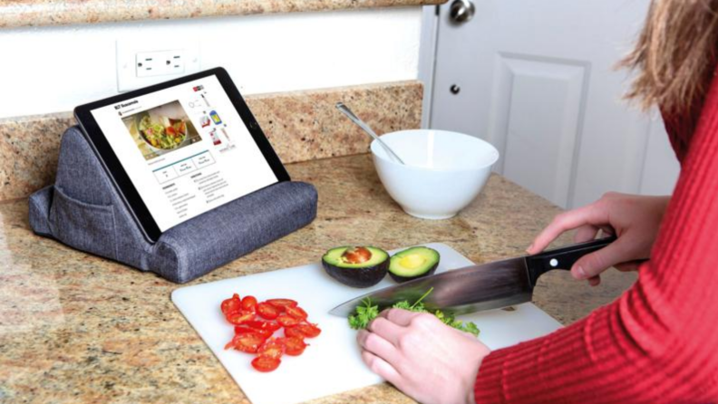 Person typing on tablet being propped up on table