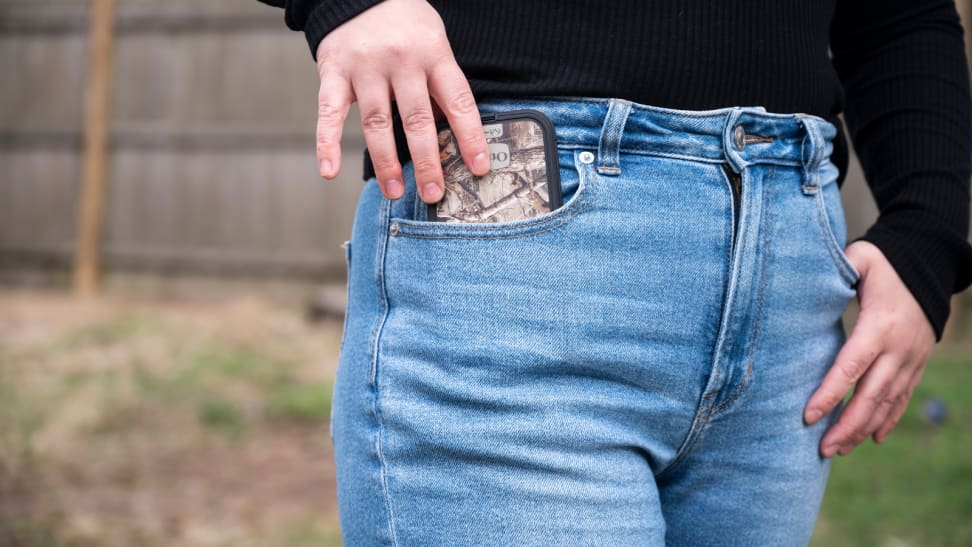 Girl wearing American Eagle jeans slides her cell phone into her pocket.