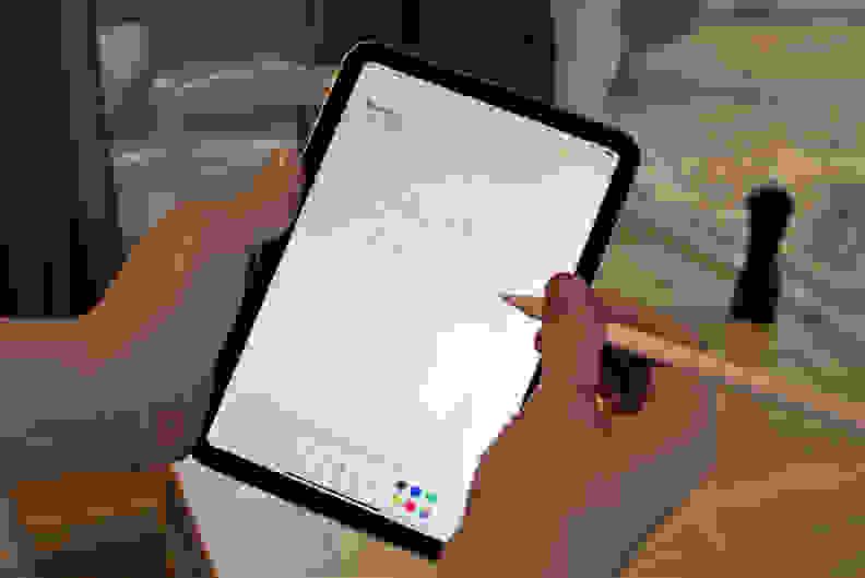 Someone writing on a computer tablet with a stylus.